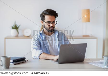Telecommuting. Eastern Man Using Laptop Computer, Sitting At Desk In Home Office