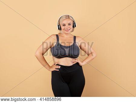 Weightloss Concept. Happy Plus Size Woman In Sporswear Posing Over Beige Background