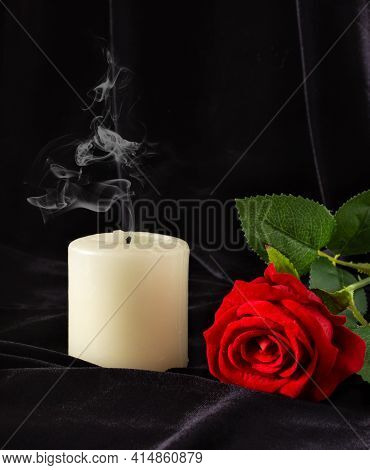 An Extinguished Candle And A Red Rose On A Black Background. The Concept Of Mourning, Condolences, F