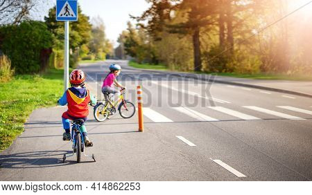 Cute Children Riding On Bicycles On Asphalt Road In Summer.