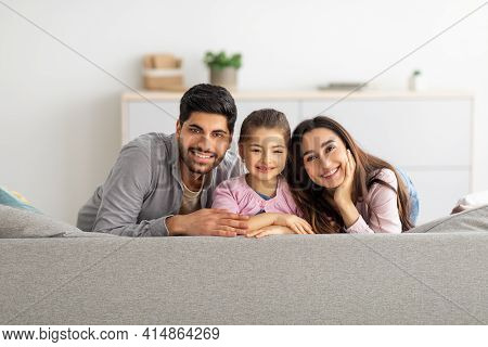 Happy Family Portrait. Happy Arab Mother, Father And Daughter Cuddling And Smiling To Camera On Couc