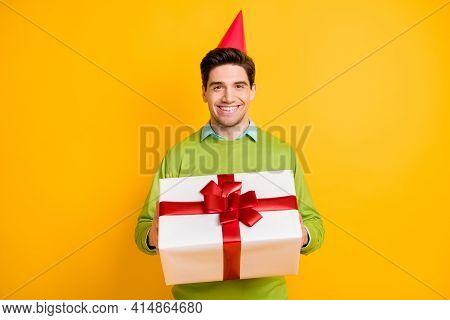 Portrait Of Nice Cheerful Guy Wearing Festal Cap Bringing Big Large Giftbox Isolated On Vibrant Yell