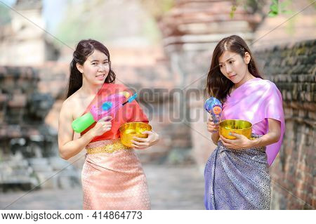 Attractive Thai Lady In Traditional Thai Dress Holding Lotus Flowers Playing With Friends On The Tha