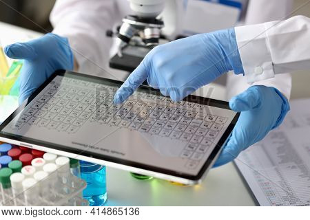 Scientists Chemists Looking At Digital Tablet With Periodic Table Of Elements In Laboratory