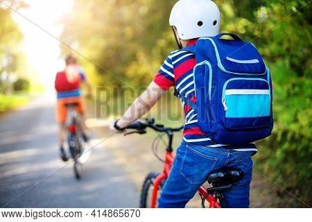 Children With Rucksacks Riding On Bikes In The Park Near School. Pupils With Backpacks Outdoors.