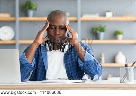 Migraine Attack. African American Man Suffering From Headache At Workplace While Working On Laptop