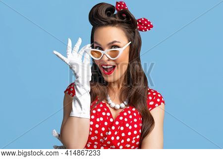 Portrait Of Excited Pin Up Woman In Polka Dot Dress, Headband And Gloves Touching Her Sunglasses On