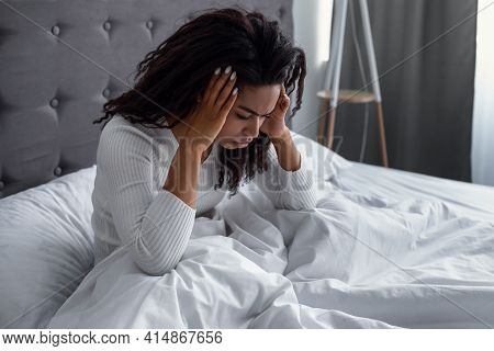 Black Woman Suffering From Headache Or Migraine In Bed