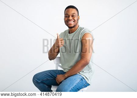 Cheerful Vaccinated Black Man Gesturing Thumbs-up Approving Vaccination, White Background