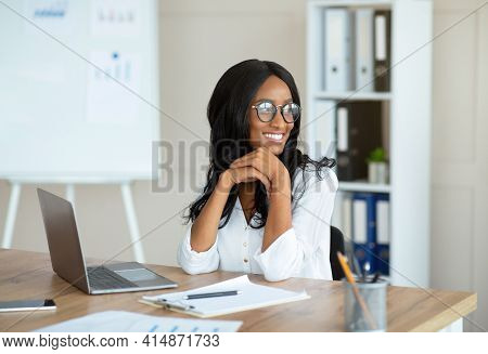Happy African American Businesswoman Having Break From Online Work, Daydreaming Near Laptop At Offic