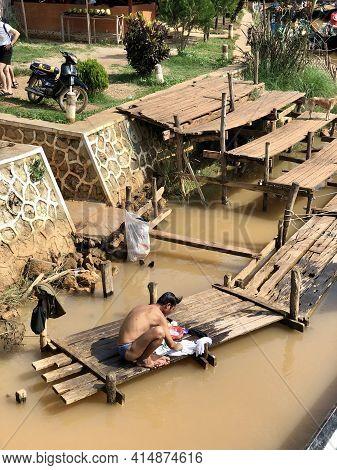 Inle Lake, Myanmar - November 9, 2019: Man Washing His Clothes In A River In Inle Lake