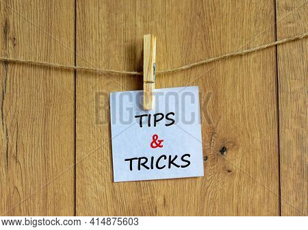 Tips And Tricks Symbol. White Paper On Wooden Clothespin. Words 'tips And Tricks'. Beautiful Wooden