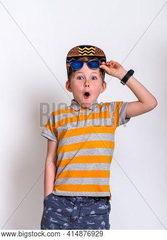 Portrait Of Cool Stylish Little Boy Wearing Sunglasses Smirking. Kid In Shades Leaning On A Blackboa