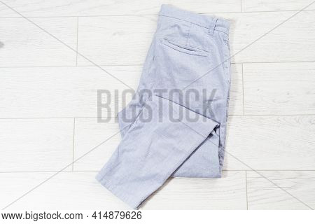 Closeup Folded Pants On White Wooden Background - Top View