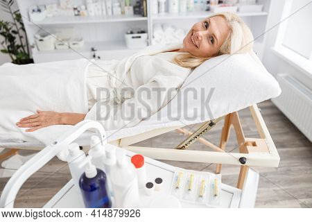 Senior Woman On The Coach Waiting For Cosmetic Procedure In Clinic Of Esthetic Cosmetology. The Conc