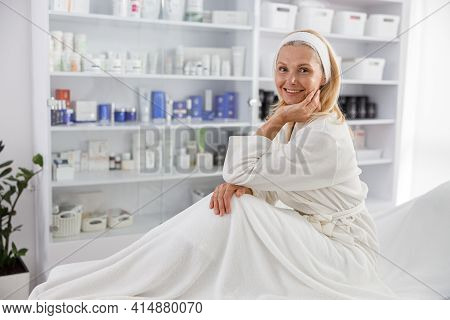 Senior Woman Smiling And Waiting For Cosmetic Procedure In Clinic Of Esthetic Cosmetology