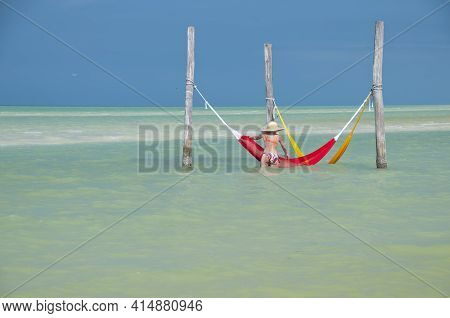 A Young Woman In A Sun Hat And Bikini Relaxes In A Hammock By The Sea On Holbox Island In Mexico. In