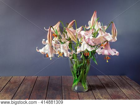 Bouquet Of Beige Colored Lilies With Pink Spots In Glass Vase On Wooden Table. View With Copy Space.