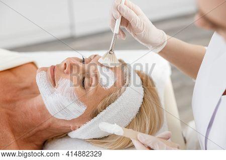 Close Up Face Peeling Mask, Spa Beauty Treatment, Skincare. Senior Woman Getting Facial Care By Beau