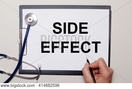 On A Light Background, A Stethoscope And A Sheet Of Paper, On Which A Man Writes Side Effect. Medica