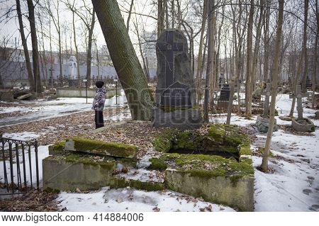 Black Headstone With Cross In Middle Of Winter Cemetery, Child In Colorful Jacket Standing In Backgr