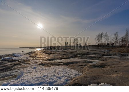 Helsinki Finland 28 March 2021 Spring Day At The Sea, People Rest On The Banks Of Uunisaari In Helsi