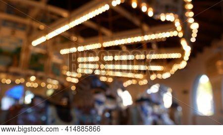 Golden Illuminated Defocused Retro Carousel Turning In Amusement Park. Blurred Shiny Merry-go-round