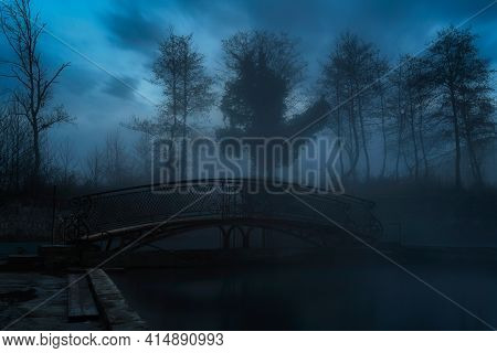 Dark Scary Park At Night. Silhouettes Of Trees Appear From The Fog. Ghost Bridge In The Center Of Th