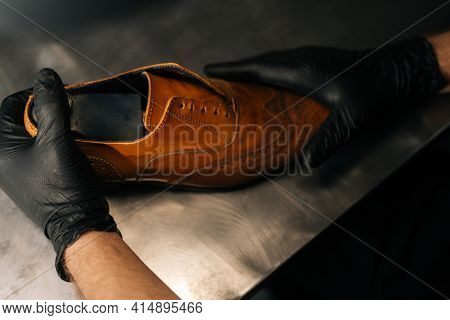 Close-up Top View Of Hands Of Shoemaker Shoemaker In Black Gloves Inserts Wooden Shoe Pad Into Worn