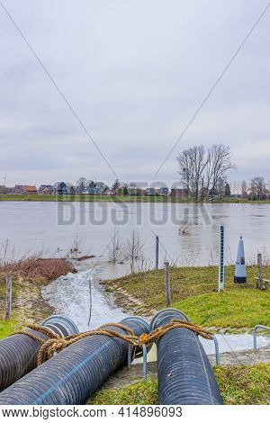Three Pipes Of A Water Pump With Water Flowing Into The Meuse River, System To Control High Levels O