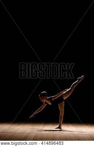 Cute Little Ballerina In Dark Ballet Costume Dancing On The Stage. Kid In Dance Class. Child Girl Is
