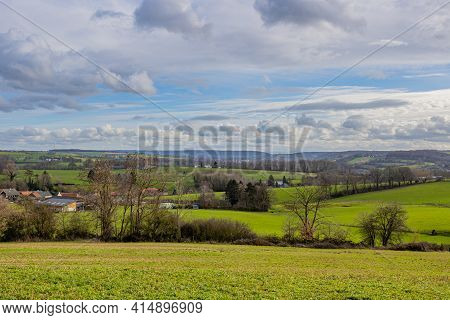 Dutch Countryside With Hills, Green Grass, Bare Trees, Farms And Small Villages In The Background, S