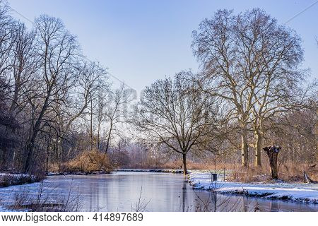 Winter Landscape With A Pond With Its Frozen Waters, Frost And Snow, Surrounded By Huge Bare Trees,