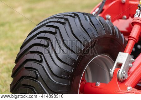 Part Of Heavy Agrarian Machinery With Black Wheel And Clean Protector On New Tire. Close Up View Of