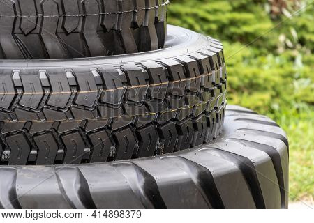 Part Of Three New Black Tire In Car Service. Concept Of Replacement And Maintenance Wheel On Automob