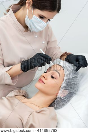 A Female Cosmetologist Or Dermatologist Making A Patient Facial Procedure In The Cosmetology Office.