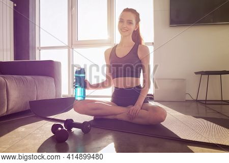 Young Woman With A Bottle Of Water The Bottle After Doing Physical Training Exercises At Home On The