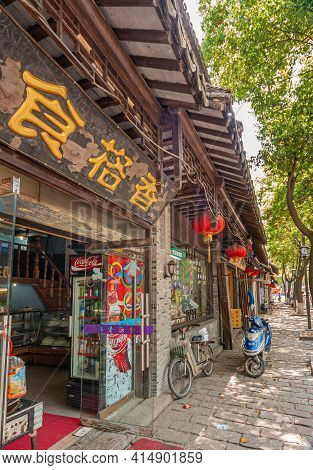Tongli, China - May 2, 2010: Rows Of Small Shops With Dark Wooden Eaves Above. Some Green Foliage On