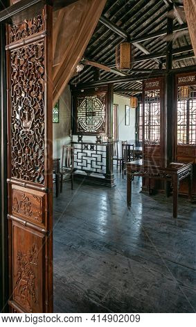 Tongli, China - May 2,  2010: Artfully Carved Brown Wooden Room Screens In Hall With Blackened Ceili
