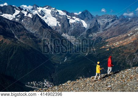 Young Couple Doing Nordic Walking In The Mountains, Rear View. An Active Couple Is Engaged In Hiking