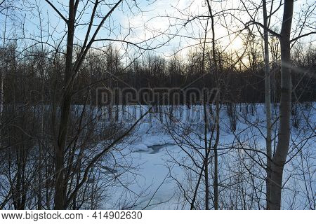 View Through Trees To A Frozen Lake In Winter