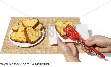 Hand Holds Clip So That Heart Shaped Cupcake Puts It On Napkin In Other Hand. Isolated On White Back