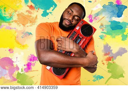 Man Hugs An Old Stereo. He Love The Music. Yellow Background
