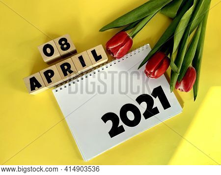 April 8 On Wooden Cubes.next To It Are Tulips And A White Notebook With The Inscription 2021 On A Ye