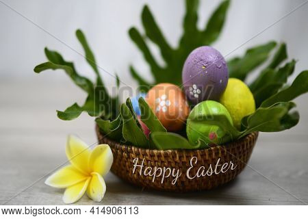 Happy Easter Text On Basket With Easter Eggs And Yellow Flower. Sets Of Colorful Easter Eggs With Di