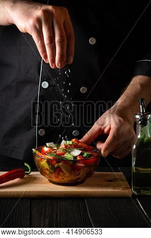 The Cook Sprinkles Salted Fresh Vegetable Salad In A Plate On A Wooden Table. Cooking Healthy Food I