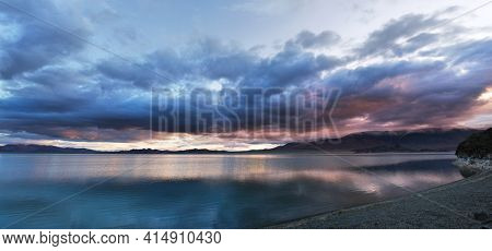 The evening cloudy sky is reflected in the Tolbo Nuur Lake