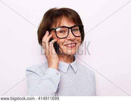 Happy senior woman using mobile phone over white background. Beautiful stylish elderly lady talking on cellphone.