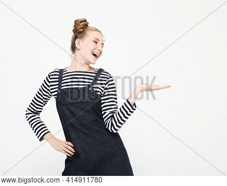 Beautiful young woman wearing a striped shirt over white background surprised, showing and pointing something that is on her hand surprised, showing and pointing something that is on her hand