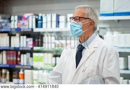 Masked doctor pharmacist working in his pharmacy, coronavirus concept